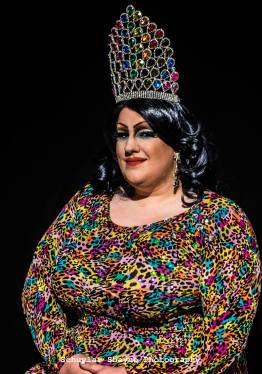Ida Carolina seated wearing rainbow cheetah print in the Miss TriPride crown